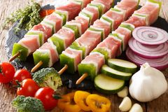 Raw shish kebab with green pepper on skewers close-up and vegetables, herbs. horizontal. Raw shish kebab with green pepper on skewers close-up and vegetables royalty free stock photo