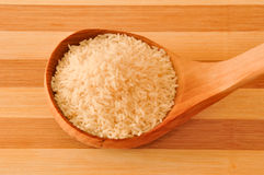 Raw short rice on the wooden spoon Stock Photography