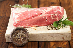 Raw shoulder lamb on wooden board and table. With 1lb iron weight stock photos