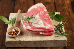 Raw shoulder lamb on wooden board and table Royalty Free Stock Images