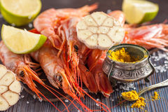 Raw shrimp, garlic, lime, curry and sea salt on a dark wooden background Royalty Free Stock Images