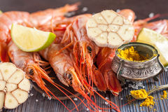 Raw shrimp, garlic, lime, curry and sea salt on a dark wooden background Royalty Free Stock Photography