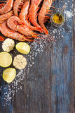 Raw shrimp, garlic, lime, curry and sea salt on a dark wooden background Royalty Free Stock Photos