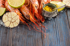 Raw shrimp, garlic, lime, curry and sea salt on a dark wooden background Stock Photos