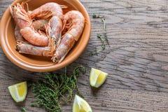 Raw shrimps with lemon wedges Stock Image