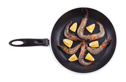 Raw shrimps on pan with lemon. Royalty Free Stock Photography