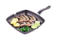 Raw shrimps on pan with lemon. Stock Image