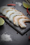 Raw shrimps on a stone plate. On a black table Stock Photo
