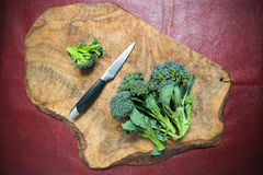 Raw sicilian broccoli and knife on wooden cutting board Royalty Free Stock Photography