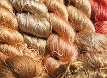 Raw silk thread. Beautiful gold raw silk woven into the garment stock photos