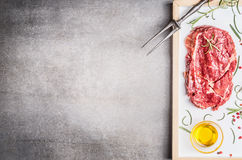 Raw Sirloin steak with meat fork , oil and herbs on stone background, top view, place for text Stock Photo