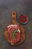 Raw sirloin steak with rosemary on cutting board. Ready for the barbecue, Top view, vintage toned image, blank space Royalty Free Stock Photos