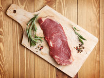 Raw sirloin steak with rosemary and spices on cutting board Stock Images