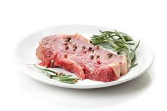 Raw sirloin steak with rosemary and spices on plate Stock Photo