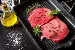 Raw sliced beef on plate pot on black Royalty Free Stock Photos