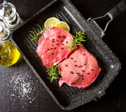 Raw sliced beef on plate pot on black Stock Photography