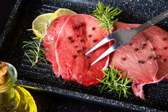 Raw sliced beef on plate pot on black Royalty Free Stock Image