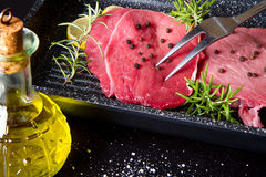 Raw sliced beef on plate pot on black background Royalty Free Stock Photography