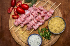 Raw slices turkey skewers couscous herbs cherry tomatoes and garlic sauce on round cutting board  wooden rustic background clos Royalty Free Stock Images