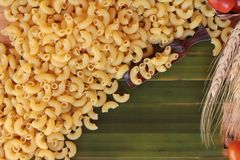 Raw small yellow macaroni pasta for cooking. Stock Image