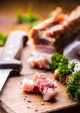 Raw smoked bacon slices on wooden board with cumin and herbs Royalty Free Stock Images