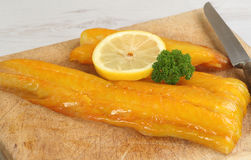 Raw smoked haddock. Fillet of uncooked smoked fish, haddock with lemon and parsley Stock Photos