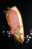Raw smoked sliced bacon with herbs on dark board Stock Images