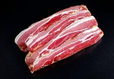 Raw smoked streaky sliced bacon on black board background Stock Photography