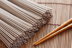 Raw soba noodles. And chopsticks on bamboo napkin. Soba is a type of thin Japanese noodle made from buckwheat flour. Close-up Royalty Free Stock Photo
