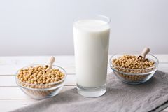 Raw soy seeds and glass of milk on slate background. Organic farming. Soymilk may be used as a substitute for dairy milk by individuals who are vegan or lactose stock image