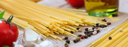 Raw spagetti pasta with vegetables. And olive oil Royalty Free Stock Photography