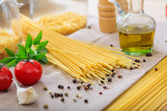 Raw spagetti pasta with vegetables. And olive oil Royalty Free Stock Images