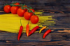 Raw spaghetti bavette with tomatoes, pepper ingredients for cooking Italian pasta. Fresh vegetables and uncooked italian pasta on. Closeup of raw spaghetti Royalty Free Stock Photo