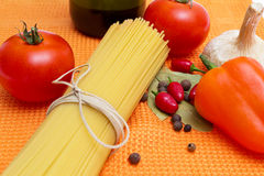 Raw spaghetti and few fresh tomatoes Stock Images