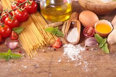 Raw spaghetti and ingredients. On wood background Stock Images