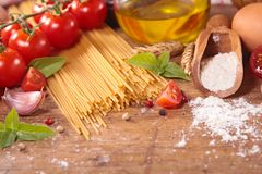 Raw spaghetti and ingredients. On wood background Royalty Free Stock Photo