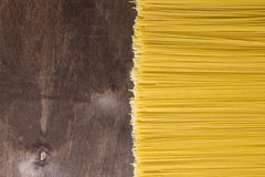 Raw spaghetti noodles. On a wooden background Royalty Free Stock Photos