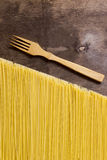 Raw spaghetti noodles. On a wooden background Royalty Free Stock Photo