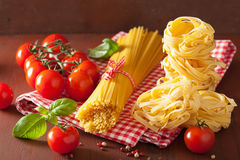 Raw spaghetti pasta basil tomatoes. italian cuisine in rustic ki Royalty Free Stock Photo