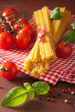Raw spaghetti pasta basil tomatoes. italian cuisine in rustic ki Stock Photography