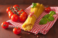 Raw spaghetti pasta basill tomatoes. italian cuisine in rustic k Royalty Free Stock Photography