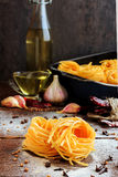 Raw spaghetti or pasta with flour, sunflower oil, garlic, pepper and spice on black background, front view place for Stock Photography