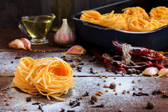 Raw spaghetti or pasta with flour, sunflower oil, garlic, pepper and spice on black background, front view place for Royalty Free Stock Photos