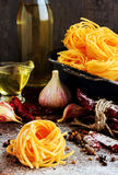 Raw spaghetti or pasta with flour, sunflower oil, garlic, pepper and spice on black background, front view place for Royalty Free Stock Photography