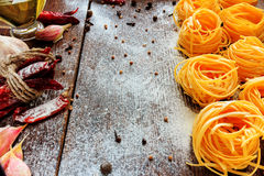 Raw spaghetti or pasta with flour, sunflower oil, garlic, pepper and spice on black background, top view place for text Stock Image