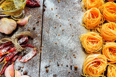 Raw spaghetti or pasta with flour, sunflower oil, garlic, pepper and spice on black background, top view place for text Stock Photography