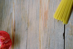 Raw spaghetti pasta and half tomato on wood background stock photo
