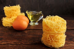 Raw spaghetti or pasta with sunflower oil and eggs on black background, front view place for text Stock Photos