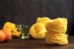 Raw spaghetti or pasta with sunflower oil and eggs on black background, front view place for text Royalty Free Stock Image