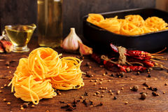 Raw spaghetti or pasta with sunflower oil, garlic, pepper and spice on black background, front view place for text Royalty Free Stock Photography